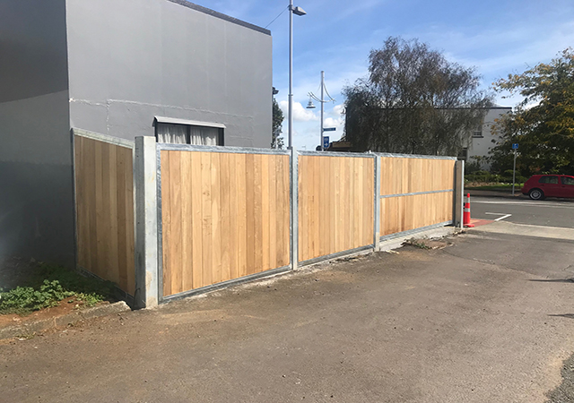 6 meter sliding gate and panels with wooden infill for a commercial parking lot